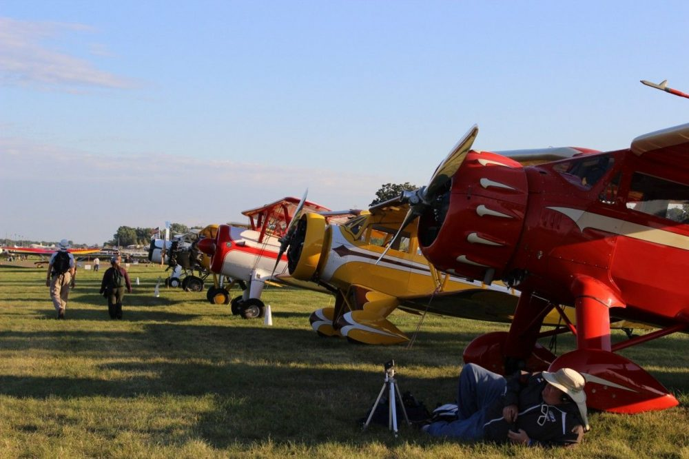 Vintage planes lined up in a field at AirVentures in Oshkosh, WI