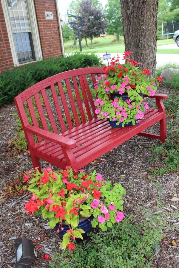 A beautiful red bench with planters of impatiens as a summery accent.