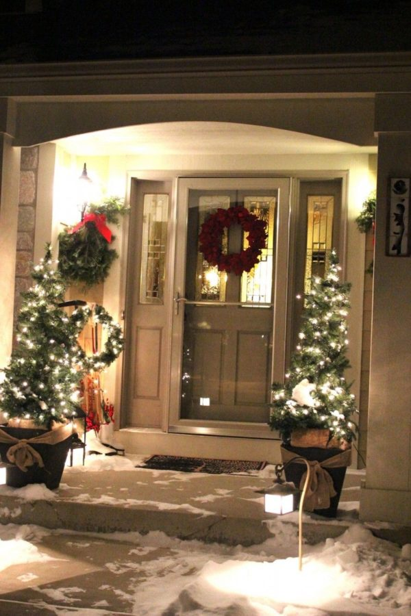 Christmas trees with white lights in planters and green swags under outdoor lights