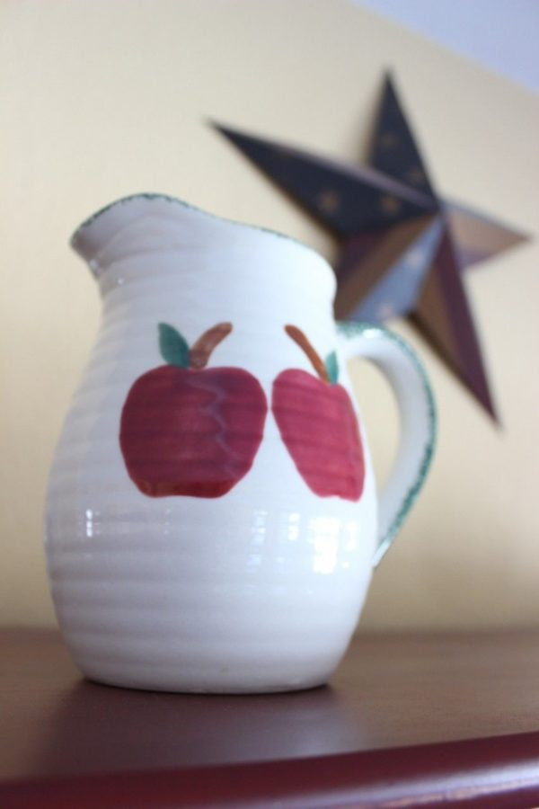 a white pitcher with big red apples that will be spray painted white.