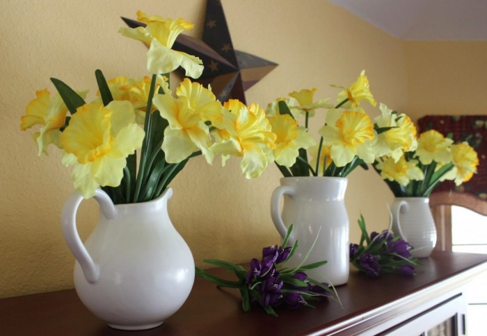 white pitchers with daffodils in them.