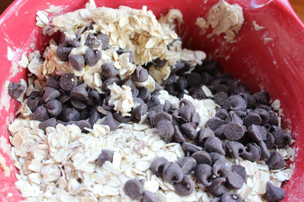adding chocolate chips to the oatmeal cookie dough