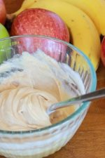 peanut butter fruit dip with apples and bananas in the background