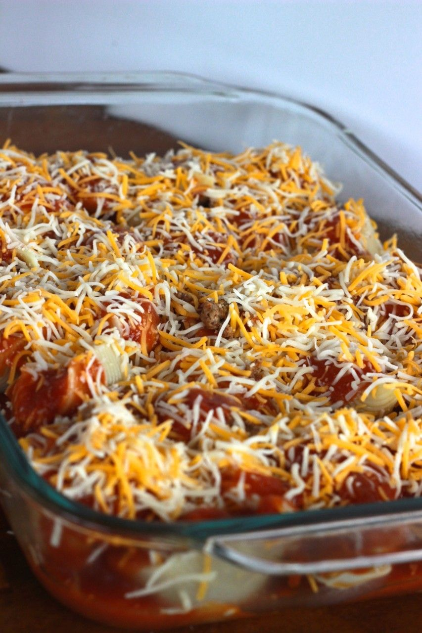 casserole dish full of large pasta shells filled with taco meat covered with cheese