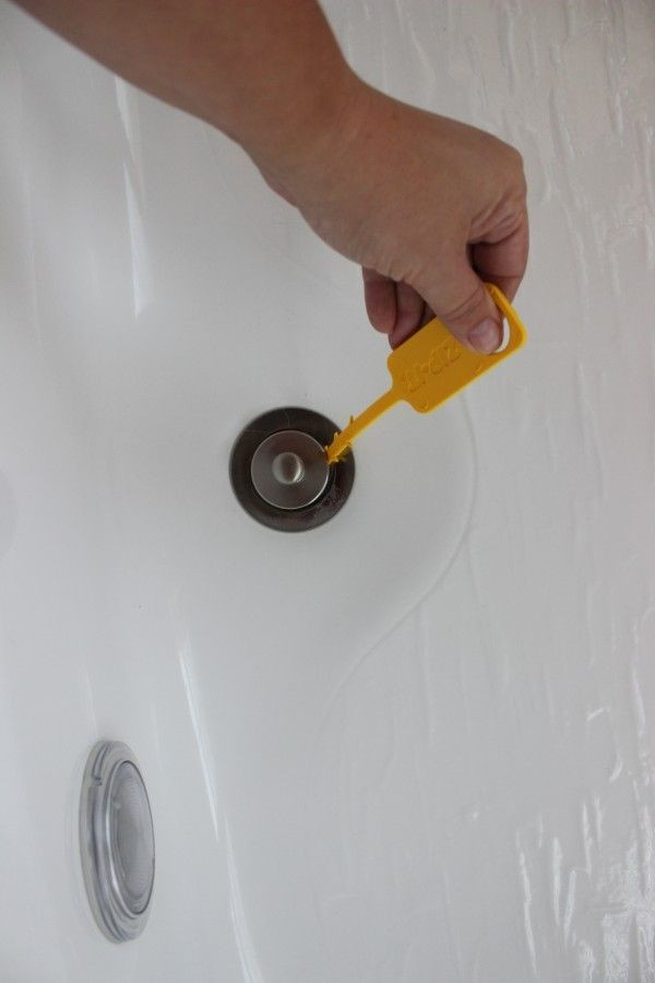 Plastic tool is pushed down the bathtub drain.