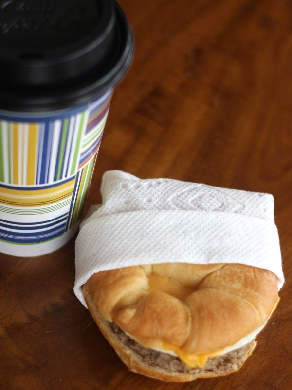 A breakfast sandwich wrapped  to go with a coffee