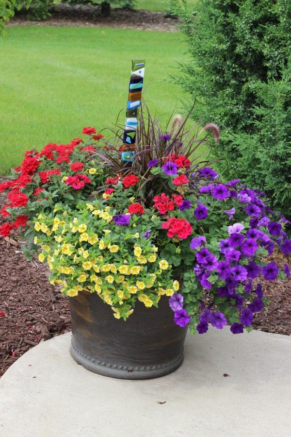 Beautiful planter with red, purple and orange flowers.