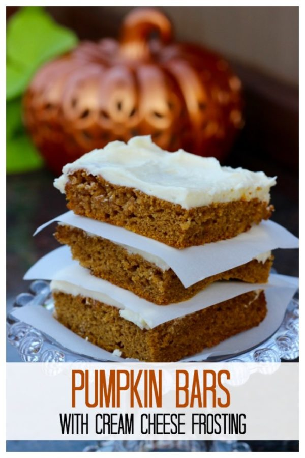 Three pumpkin bars with cream cheese frosting .