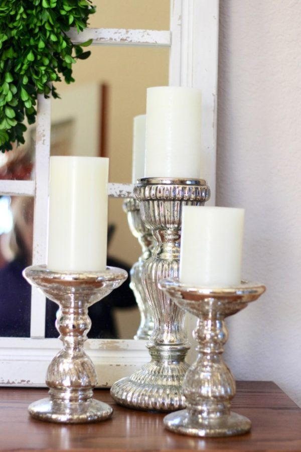 white candles on mercury glass candle holders sitting in front of a chippy white farmhouse mirror