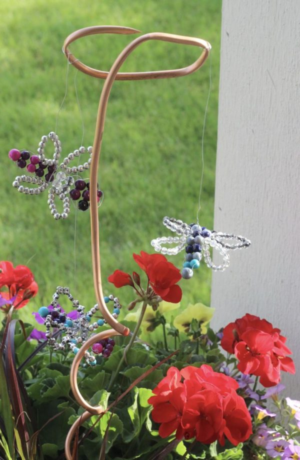 Beaded dragonfly planter decorations hanging from twisted copper pipe.