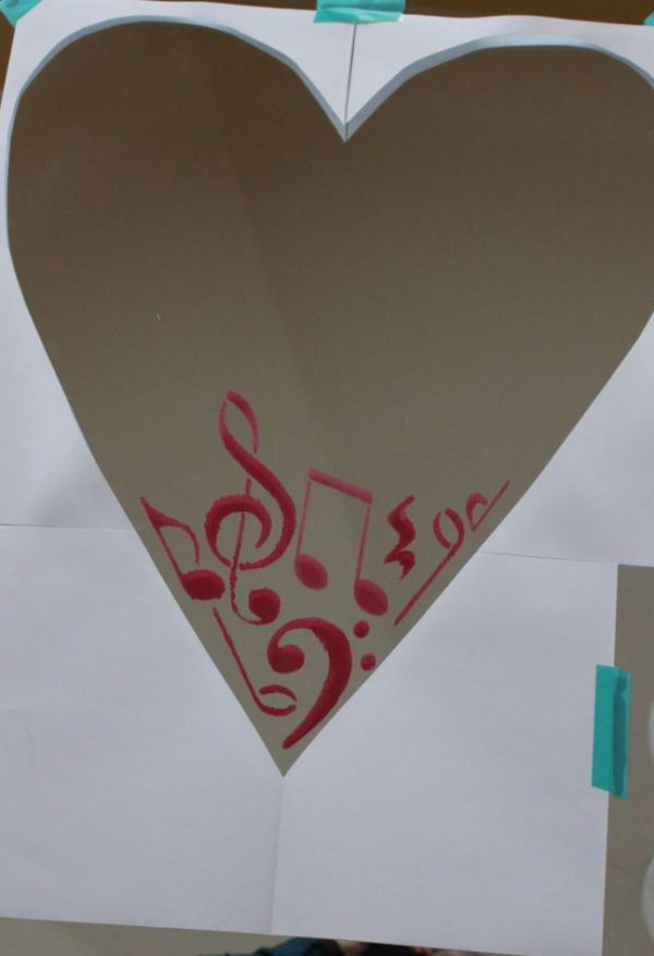 heart shaped template on a mirro being filled with red painted musical notes