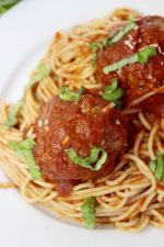 Meatballs covered in spagetti sauce, sitting on spagetti noodles.