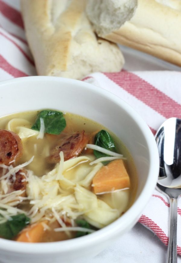 a bowl of soup with sliced brats, ravioli, cut up squash and spinach.