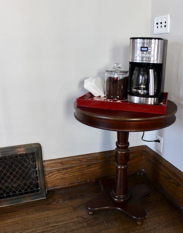 Original coffee station with the coffeemaker on a red tray on an end table.