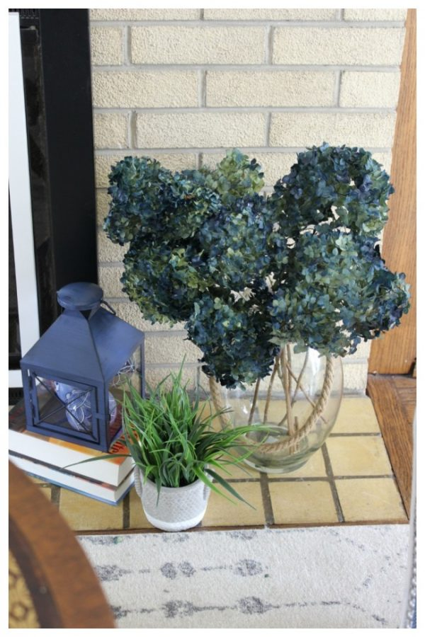 A display beside the fireplace containing blue annabelle hydrangeas, a blue lamp and a small green leafy plant.