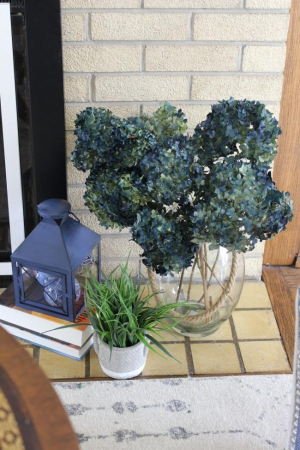 blue lantern with a large vase of blue hydrangeas