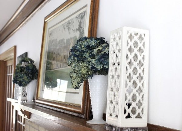 A very simple mantle in my vintage 1920's home. A print of an old English manor house, blue dried hydrangeas and some lighting on my mantle.