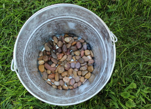 galvanized pail with a layer of stones