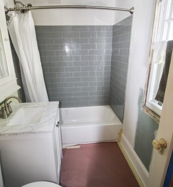 The bathroom with a white tub and a grey surround.