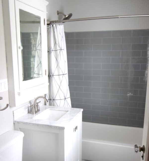 completed bathroom with white vanity and tub. There is a grey surround for the bathtub.