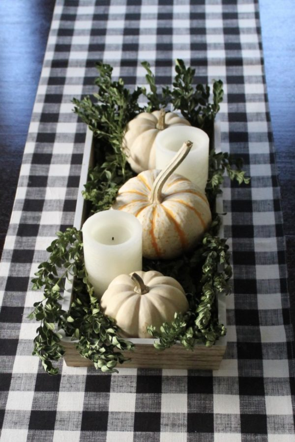 Centerpiece tray with white pumpkins, boxwood branches and white candles.