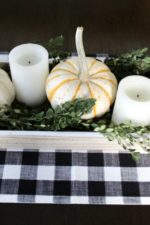 fall dining room table centerpiece with white pumpkins, candles and some green boxwood branches