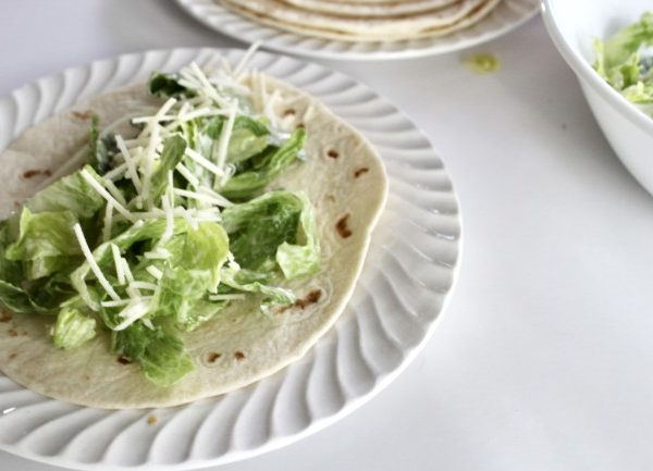 A Caesar Salad with grated parmesan on a fresh tortilla.