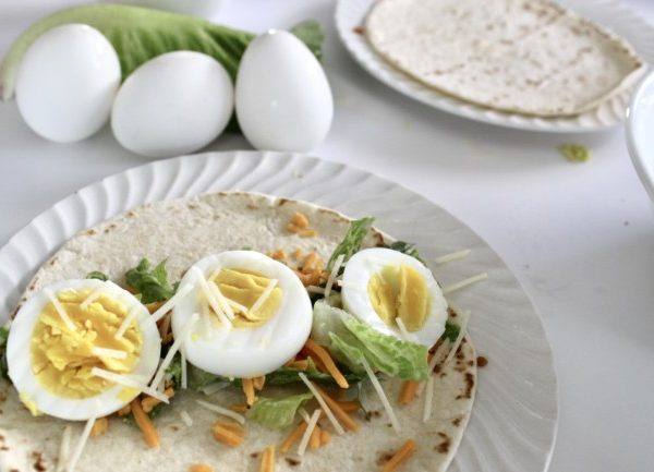a wrap with caesar salad on a tortilla, with a sprinkling of shredded cheese and sliced hard boiled eggs.