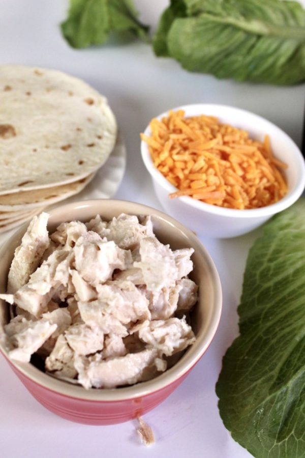small bowl of chicken salad with cheddar cheese and tortillas in the background.
