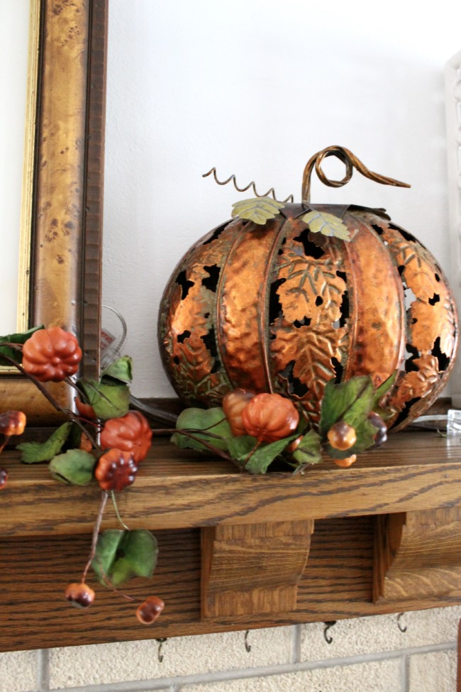copper pumpkin in front of green ceiling tin