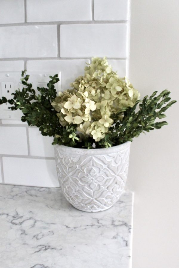 Planter fulled with dried boxwood and hydrangeas.