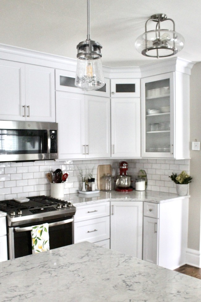 a white kitchen with white cabinets that extend to the ceiling