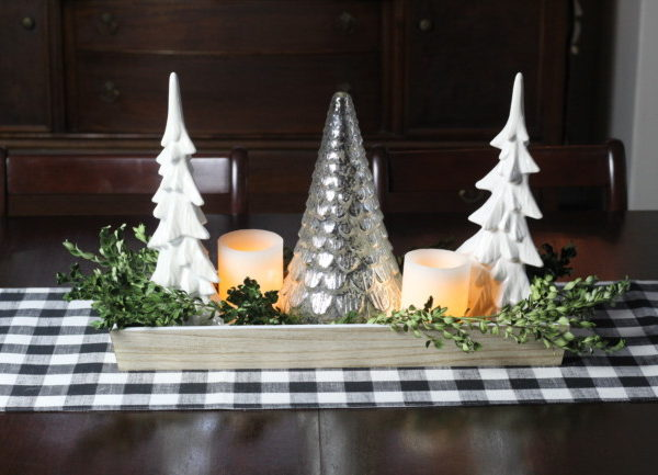 Christmas table centerpiece with two white ceramic trees, a mercury glass tree and some dried boxwood