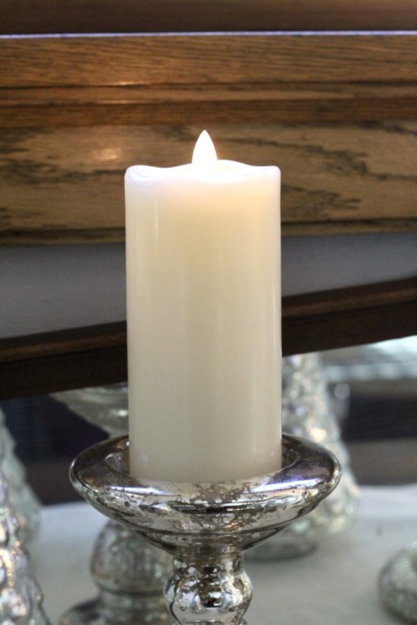White candle on a mercury glass holder