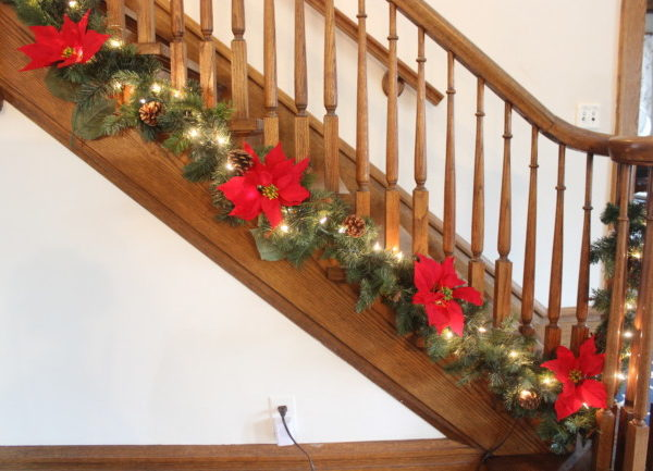 green garland with red pointsettas at the base of the banister