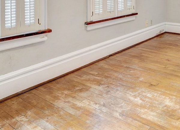 Old maple floors in damaged condition with water stains, scratches and stain worn off.