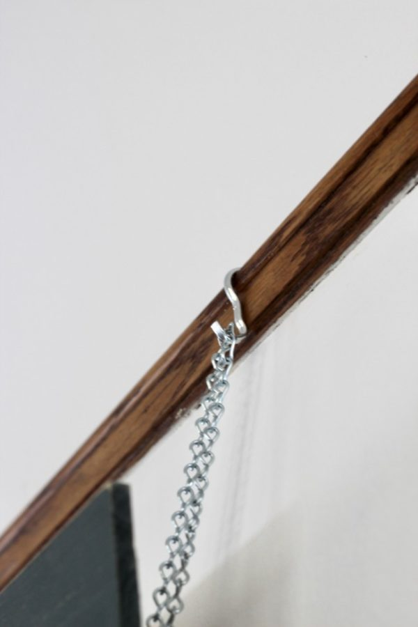 picture hook with chain hanging on a picture rail molding.
