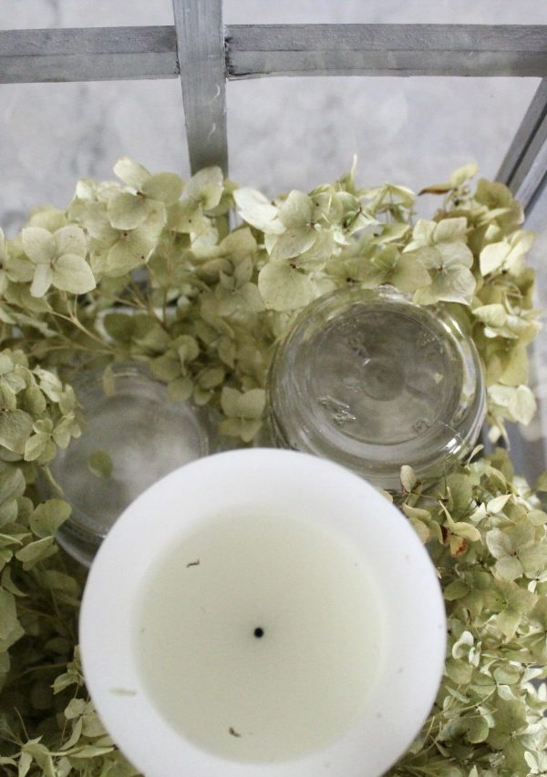 placing white candle on mason jar for height in a lantern