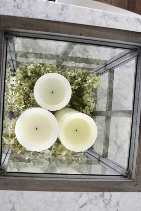Three candles on mason jars in a lantern