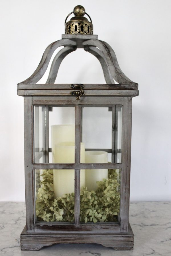 wood lantern with white candles and dried hydrangeas