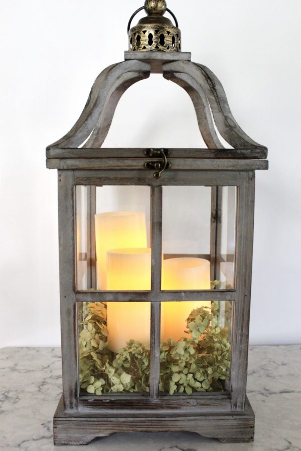 candles flickering in a wooden lantern