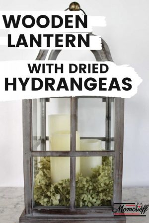 wooden lantern with white candles and dried hydrangea.
