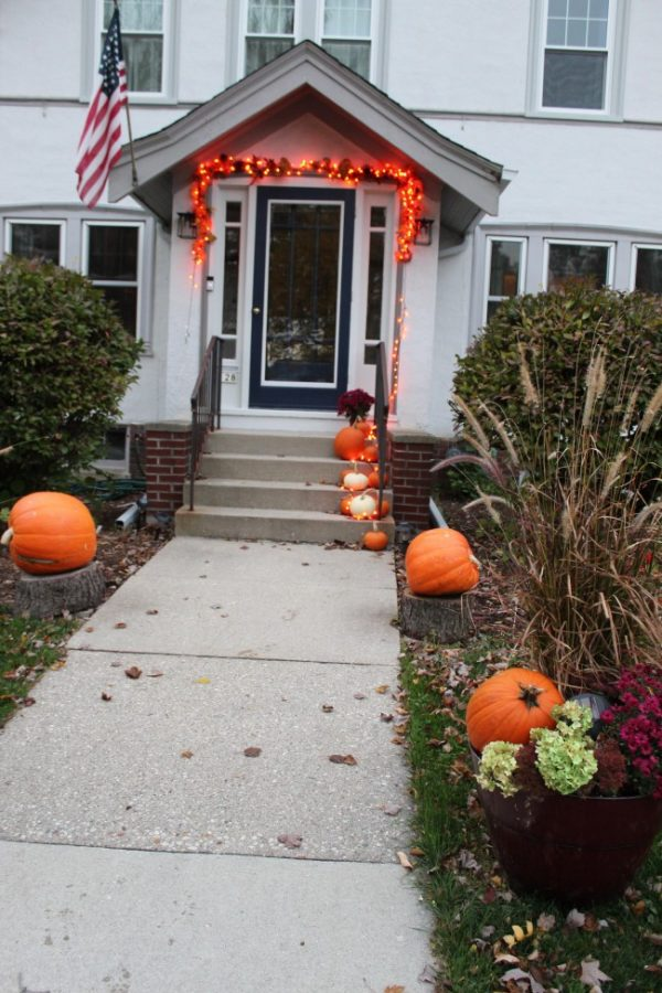 decorated fall walkway with pumpkins and fall planter
