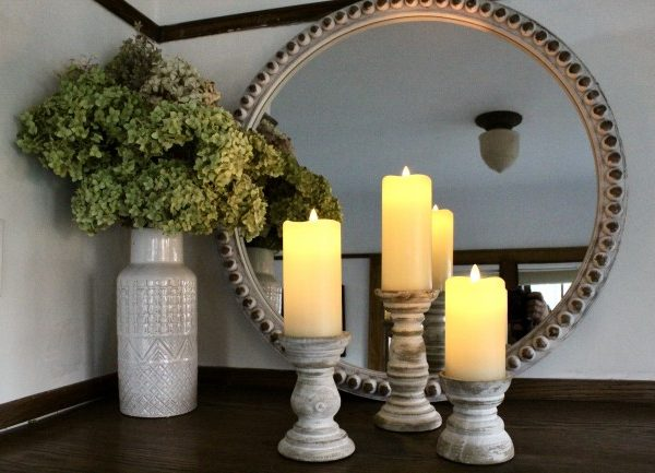 Wooden candle holders with white candles, with large round mirror in the background. Some dried hydrangeas on the left of the candles