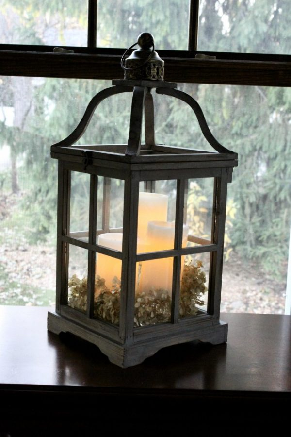 three candles glowing in a large wooden lantern in a window.