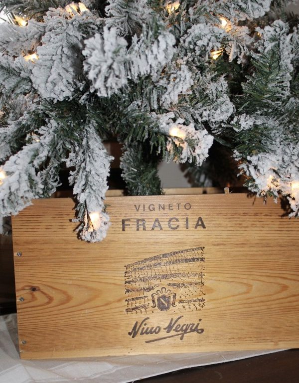 closeup of wooden wine box with a Christmas tree in it.
