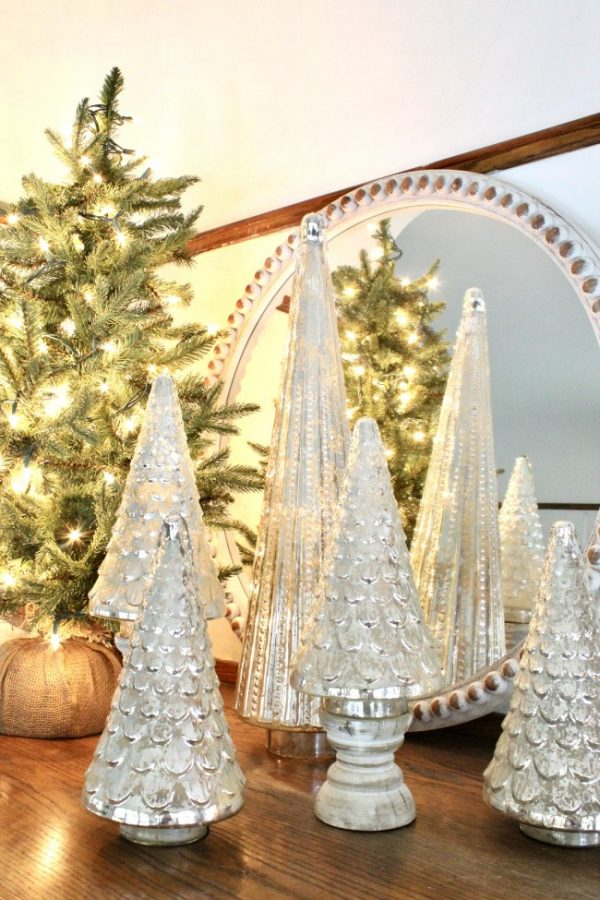 mercury glass trees on white wooden candle holders with a tree with white lights in the background