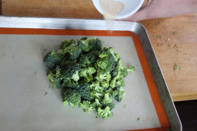 spreading garlic salt on broccoli