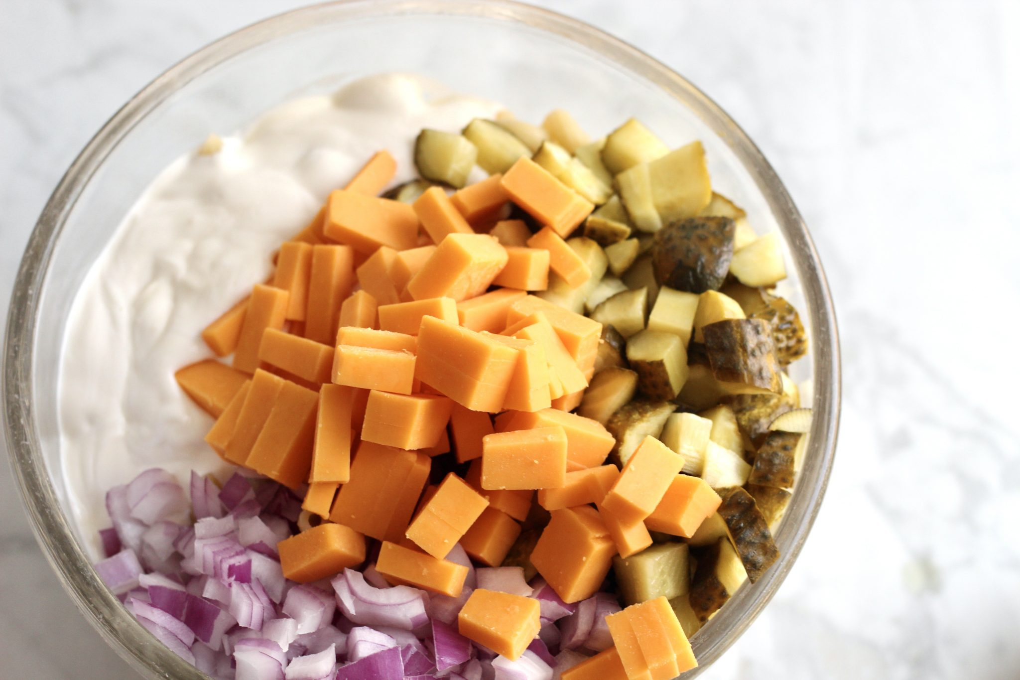 pasta in a bowl with dressing, cheese chunks, pickle chuncks and onions prior to mixing.